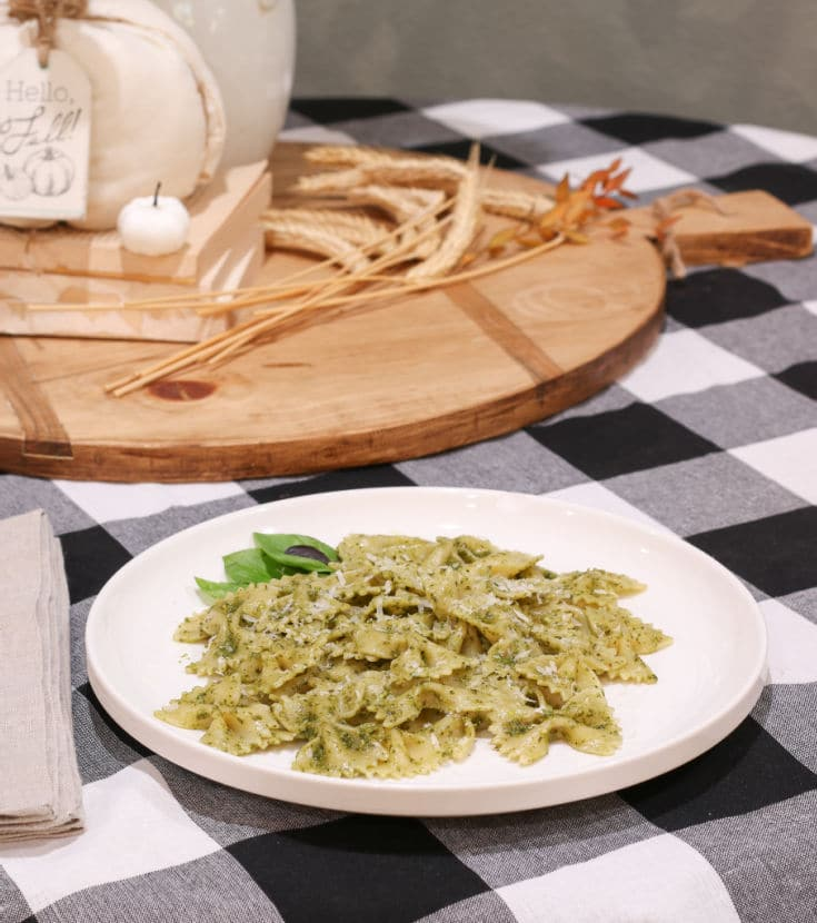 Homemade basil pesto sauce with bowtie pasta noodles on black and white buffalo plaid table cloth