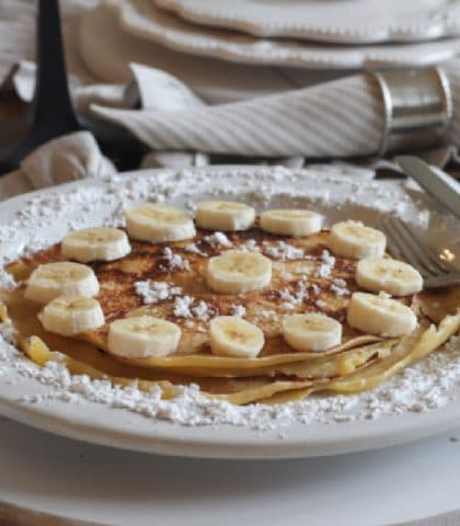 plated stack of homemade crepes with bananas and powdered sugar